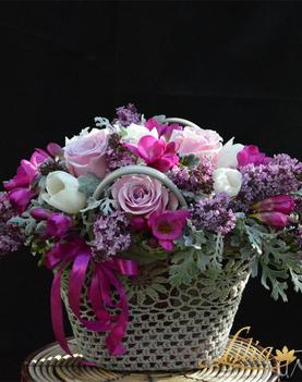 Arrangement in wicker bag with tulips, roses and freesia